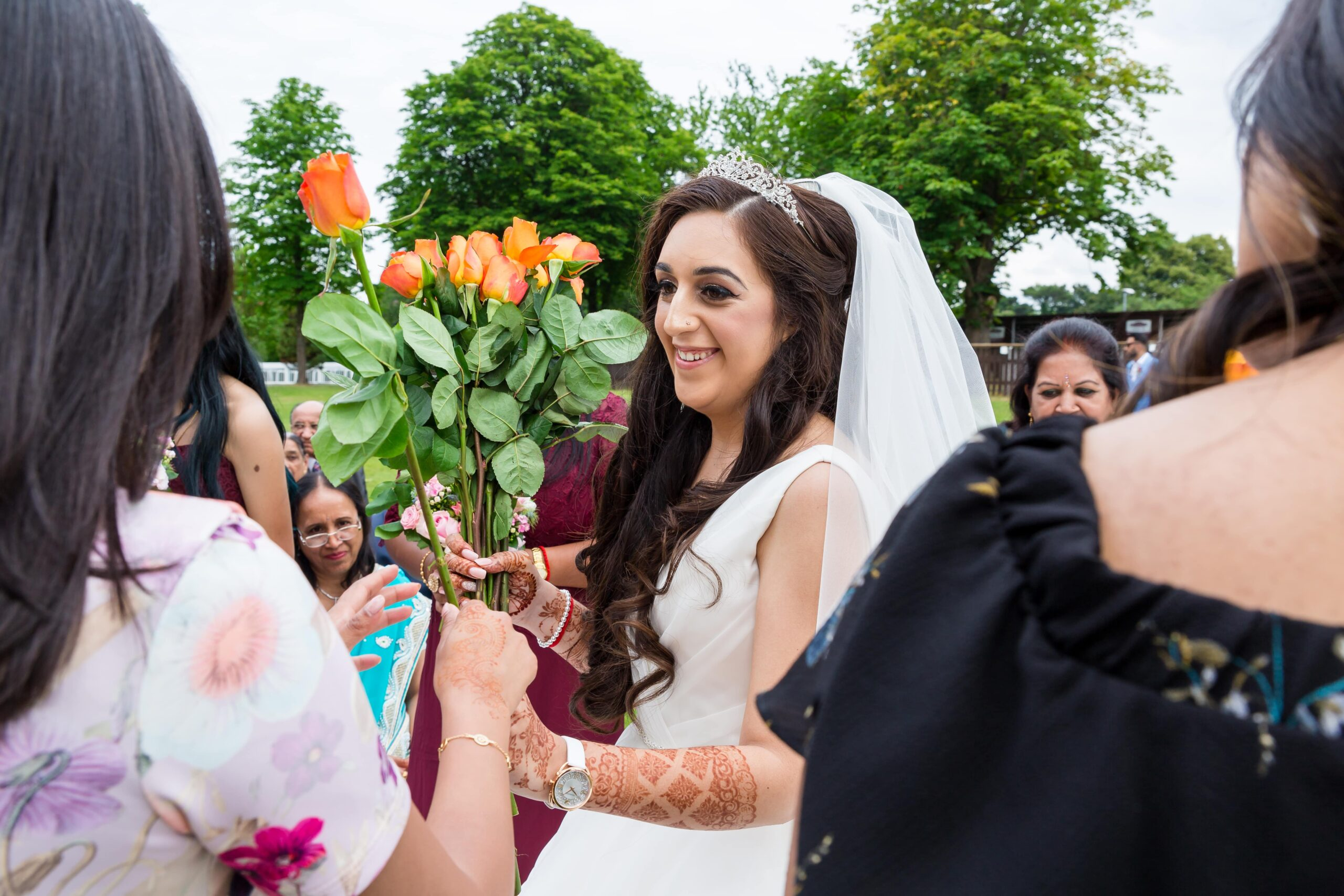 A beautiful asian bride giving guests a rose