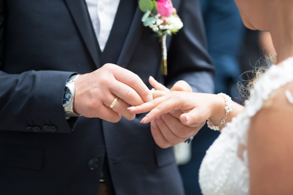 Groom placing a wedding ring on brides finger